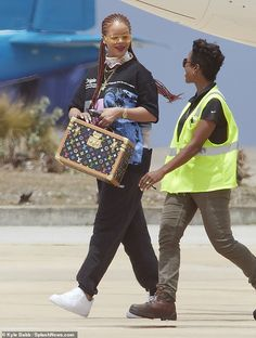 Rihanna rocks braids and futuristic shades while carrying Louis Vuitton tote in Barbados Rihanna Barbados, Rihanna Looks, Louis Vuitton Totes, Carry On, Celebrity Style, Graphic Tees, Braids, Celebrities, Celebs