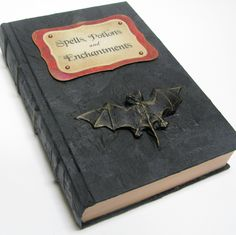 "Grab an old hardcover book, and cover it with black construction paper. Use card stock or construction paper to craft a spooky label highlighting the book's magical contents. For a finishing touch, find a small bat or spider ""talisman"" at the dime store, and glue it to the cover. Source: Etsy seller ElvesInTheAttic"