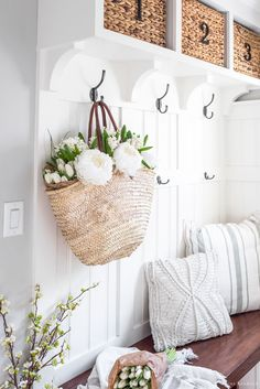 Spring Mudroom Decor | A fresh basket of flowers hangs in a mudroom decorated for Spring with throw pillows and branches.
