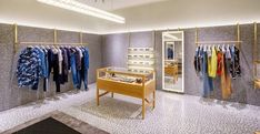 Terrazzo flooring and matching wall panels form the sleek backdrop of custom-made timber furnishings, massive marble displays and wall-mounted clothing racks in shiny brass.