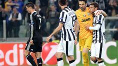 El portero del Juventus Gianluigi Buffon abraza a su compañero Claudio Marchisio tras el final del partido, mientras el delantero del Real Madrid Cristiano Ronaldo abandona el terreno.