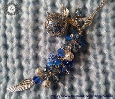 Käfig mit Flügeln und Strass-Klangkugel in hellblau, dazu farblich passend ein langer Perlenanhänger mit Flügel.