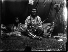 Glass negative (black and white); portrait of Tried to Fly, a Blackfoot chief, seated inside a tipi, wearing a decorated, fringed shirt, decorated leggings, neck ornaments, ear ornaments, and his hair in braids, he is holding a pipe; a Blackfoot girl wearing a decorated dress, and bead neck ornaments is seated next to him; several items of clothing, and pots are on the floor next to him; Gleichen Reservation, Canada.  Photographic process