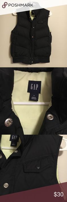 Down vest This vest is thick, puffy, and warm but also very light and comfortable. It is black with a bright yellow/green interior. It snaps all the way up and has one small chest pockets and two regular hand pockets lined with fleece. Gap Jackets & Coats Vests