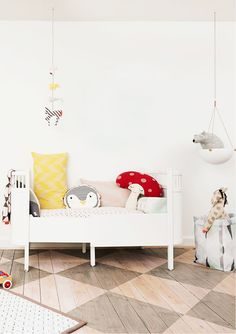 Lovely white nursery with checkerboard hardwood floor and pops of red and yellow.
