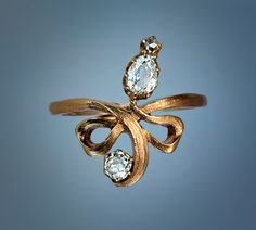 An Art Nouveau Ribbon Ring    This elegant antique rose gold ring is designed as an elaborately tied ribbon with a    prong set pear shaped diamond (approximately 0.22 ct), an old mine, and a rose cut diamond.     Total diamond weight approximately 0.5 ct.    The ring was made in Moscow between 1899 and 1908.