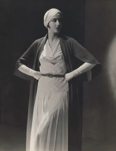 Model is wearing a crepe dress with a white turban, gloves and black sleeved cape, by Vionnet, 1931. Photo by George Hoyningen-Huene.