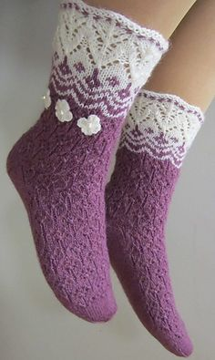 "These socks were designed as as ""sisters"" to my leaf-patterned Helmike-socks. Knitted on double pointed needles, I combined lovely lace cuff with some stranded pattern and lace with small flowers. Any other color instead of violet or orange would look great and shiny with white. Or maybe instead of white some other color? :)"