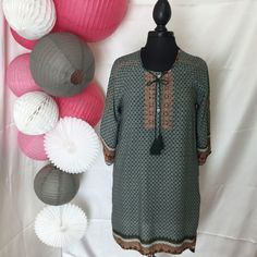 Most Comfy dress!! Higher hem in front and lower hem in back is too cute!! Embroidery accents the chest along with a tassel tie. Multi print and color patterns make for interesting eye catching detail