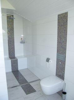 Schimmernde Mosaikfliesen zieren Dusch- und WC-Bereich