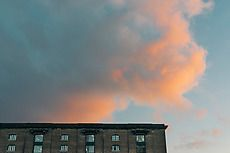 Architectural building at Granary Square in UK against colorful sky. Architecture gallery by Trent Lanz for Stocksy United - Royalty-Free Stock Photos. air, architecture, atmosphere, background, beautiful, blue, blue sky, brick, building, city, cloud, cloudscape, color, colorful, concept, dream, evening, fluffy, foor, from below, heaven, horizontal, morning, natural, nobody, old, orange, outdoors, peaceful, picturesque, pink, scene, sky, summer, sunlight, sunrise, sunset, uk, urban, view