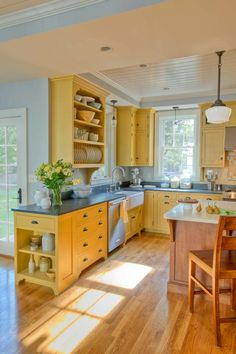 Kitchen with yellow cabinets and grey counters -- Crown Point Cabinetry