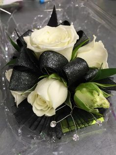 Wristlet corsage with white spray roses, black and silver ribbon, clear rhinestones and black accents. #prom #corsage #wristlet #flowers #theflowershopfairoaks
