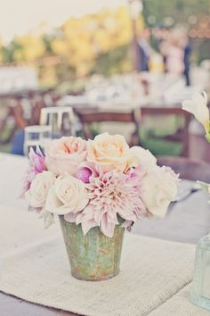 Pale dahlias and roses in a zinc bucket