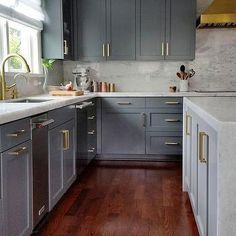 Love the Dark Gray Kitchen Cabinets with Brass Pulls (and the marble backsplash)