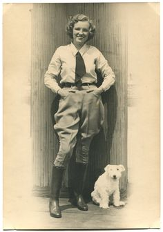 1920s-1930s woman in  jodhpurs with a terrier. Possibly Ruth Elder, aviator.