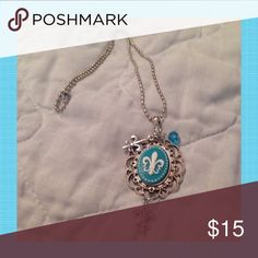 """Turquoise Fleur De Lis Necklace Turquoise resin Fleur De Lis cameo in a metal setting with dangling Crystal beads and charms. On a 24"""" stainless steel chain. Jewelry Necklaces"""