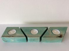 A wooden candle holder made of reclaimed wood stained in English Ivy, a blue-green colour that still allows the grain of the wood to come through. Height approx 3.5cm Width approx 8cm Length approx 32cm