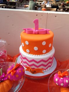 Pink and orange first birthday party in October. Tiered birthday cake