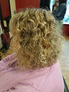 Curly angled bob with bright blonde highlights. From shoulder length.