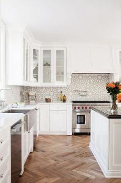All-white kitchen with patterned tile backsplash, black granite topped kitchen island counter, chrome appliances and wood herringbone floors. Wow!
