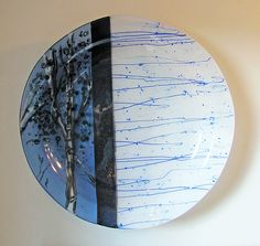 "combines opaque and transparent glass sections of blues and white. The tree design is created using glass powder in white, colored glass frit in grays, aquas and blues and then accented with black gestural detail. 2 "" h x 15"" diameter 600.00"