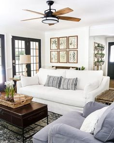 Black windows and doors bring drama to this cozy living room, vintage prints give it a sense of history