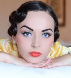 Love this look, starts w/flawless skin, sculpted brows and cheeks. Then blush on apples of cheeks, gorgeous winged eyeliner and chiseled lip with BOLD color...this screams pin-up girl to me!