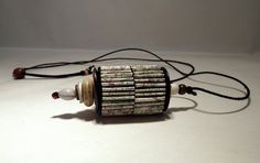 Liz Hamman, Tibetan prayer wheel inspired pendant. Pendant made from maps with seed,bone,wooden beads, mother of pearl button and cotton. Inspired by Tibetan prayer wheels.