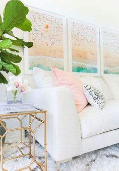 Bright living space with a white sofa, a large area rug, and large framed art