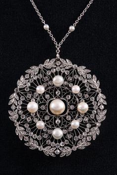 A Belle Epoque platinum, diamond and pearl pendant/brooch, circa 1910.