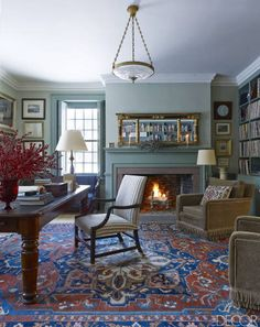 A pair of circa-1930s armchairs from John Derian and a 19th-century American table in the library; the 19th-century Persian rug was bought at auction, and the mantel is original.