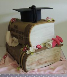 Graduation cake of stacked books. Bottom book is 8″ × 10″ layered cake and the top cake is 8″ × 6″ layered cake, the cap/hat is hollow. Customer wanted me to pretty it up a bit for her mum in law hence the bwos and flowers