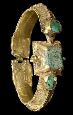 A Seljuk turquoise-set gold Bangle Persia, 12th Century the ridged, triangular section box-construction shank terminating in a double lion-head clasp and two set oval turquoises, the pyramidic bezel set with a glass rectangle and flanked by two set circular turquoises, a pin fitting at the base of the bezel, the shanks decorated with raised quatrefoils flanked by inscription-filled cartouches, all edges with granular decoration