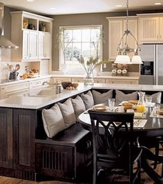 The kitchen is too cottage-y for my house, but I like the space-saving bench behind the island. -Bench in the kitchen for small kitchens