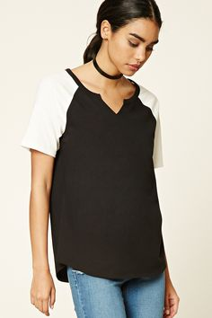 A cotton baseball tee featuring a raw-cut V-neckline, contrast short raglan sleeves, and a curved hem.