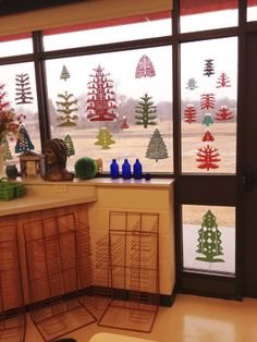 Cut paper Christmas trees in my art room windows