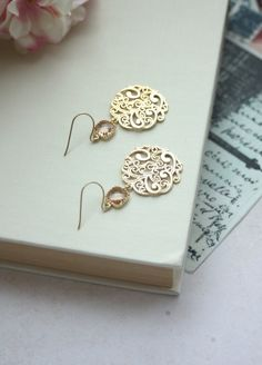 ♥´¨) ¸.•´ ¸.•*´¨) (¸.•´ ♥ ~ Gorgeous matte gold filigree beautiful intricate and details all around. It is suspended from peach glass drops and from tarnish resistant, gold plated over brass french ear wires. Lovely for the pink and gold themed wedding day or everyday earrings for yourself or someone special. Filigree measures approximately 1 inch in diameter. Total length of the earrings are approx. 2 1/4 inches. Nickel and Lead Free.  For more modern jewelry…