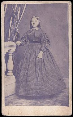 Young lady in print dress, gathered coat sleeve with trim on seam and at cuff.  Belt and bow at neck.  Fastens in front.