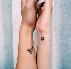 Creative couple tattoos in the form of a primitive looking spaceship and a planet with a ring around it.