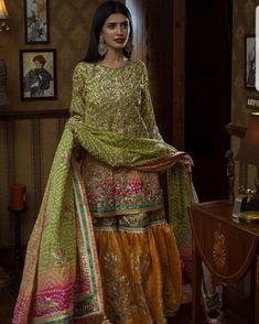 Embroidered flourishes on earthy tones with playful pink and yellow accents, this Noor Mahal piece emanates fine eastern couture. Pakistani Mehndi Dress, Pakistani Bridal Couture, Bridal Mehndi Dresses, Pakistani Wedding Outfits, Pakistani Wedding Dresses, Mehendi, Bridal Lehenga, Shadi Dresses, Indian Dresses