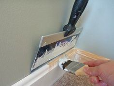 Use large drywall knife to paint trim--no more tape!