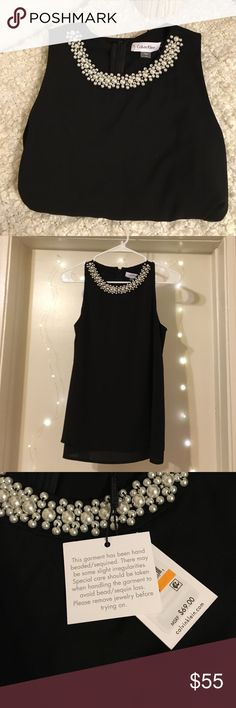 Adorable beaded neckline black sleeveless blouse Adorable flowy black sleeveless tank with pearl embellishments. 97% polyester 3% spandex. Never worn. In perfect condition! Back has a slit down the middle so that it flows nicely! Shown in photo 4. Calvin Klein Tops Blouses