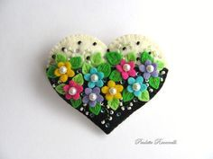 Hi Everyone!    This black and white heart pin is so eye catching. Its embellished with pretty bright flowers, swirly vines and polka dots. Made of 100% wool felt, this pin measures 2 3/4 across, by 2 3/8 from top to bottom. Its been made to keep its shape and not bend when youre wearing it, and its all hand stitched.    All of my things are made by me, in my smoke free home. Your purchase will be mailed out within two days of payment, except for items that are purchased on a Friday...