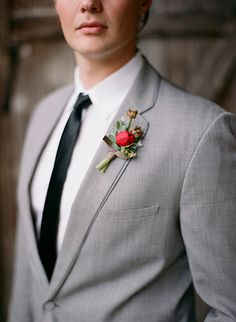 Temecula creek inn rustic wedding shoot groom heather grey suit with white dress shirt and long black skinny tie and red floral boutonniere