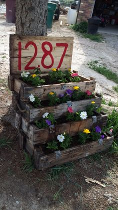 Old ammo boxes used as a flower box and house number sign