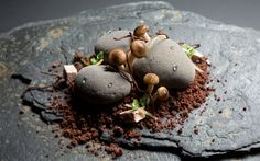 "COCOA PEBBLE DESSERT. Alpaco chocolate mousse ""stones"" topped with meringue mushrooms and served on a sprinkling of chocolate soil. A hidden spoonful of lemon curd is ensconced within each pebble, acting as a brightness to lift the rich flavors."