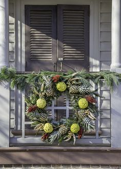 The door of the Robert Carter House in Williamsburg is not actually decorated, rather the porch is. And with a lovely wreath of osage oranges and pineapple.