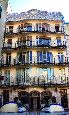 Casa Batlló  La façade intérieure est décorée de trencadis multicolores dessinant des guirlandes et des bouquets de fleurs comme des lianes qui pendraient de la terrasse. La partie haute présente une forme ondulée très dynamique qui renvoie à l'inspiration marine de Gaudí