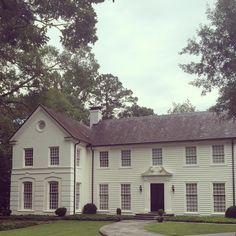 Limestone & Boxwoods - Instagram (@limestoneboxwoods) - A white on white house with black louvered door in Buckhead, Atlanta.
